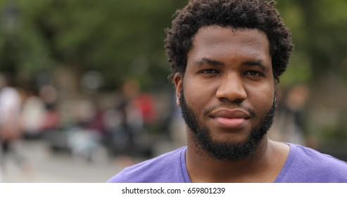 Young black man in city park face portrait serious