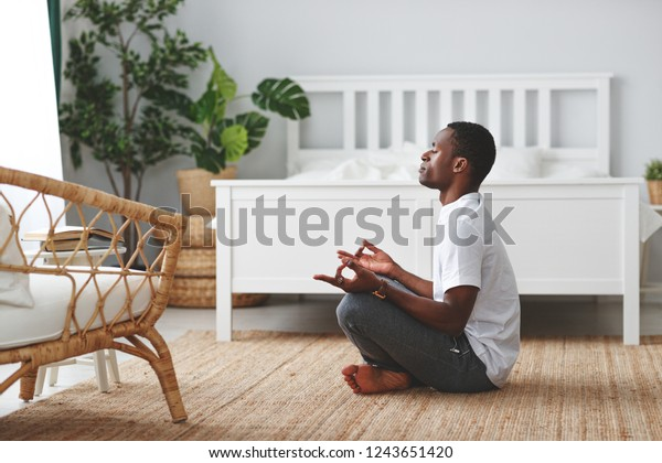 young black man doing yoga and sitting in lotus position at home in the bedroom