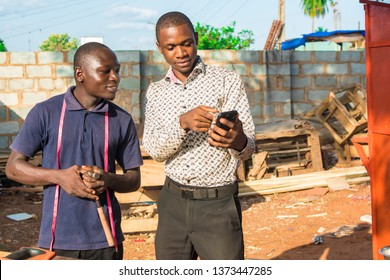 young black man dressed corporate talking to a local carpenter showing him something on his phone