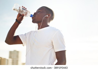 Young black man drinking water.