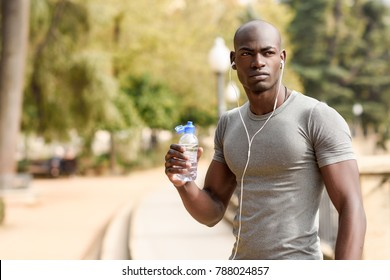 Young black man drinking water before running in urban background. Young male exercising with naked torso listening to music with headphones.