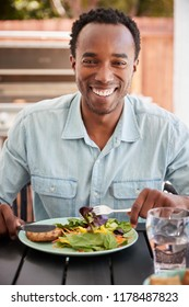 Young black man eating lunch at a table outside, vertical