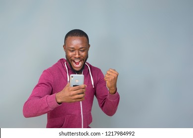 young black man excited and celebrating while holding and looking at his phone
