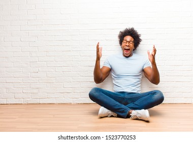 young black man furiously screaming, feeling stressed and annoyed with hands up in the air saying why me sitting on the floor at home