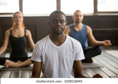 Young black man and a group of sporty people practicing yoga lesson with instructor, sitting in Sukhasana exercise, Easy Seat pose with mudra gesture, students training in club, working out, close up