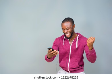 young black man happy and excited and celebrating while looking at his mobile phone