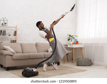 Young black man having fun during cleaning house, playing with vacuum cleaner at living room