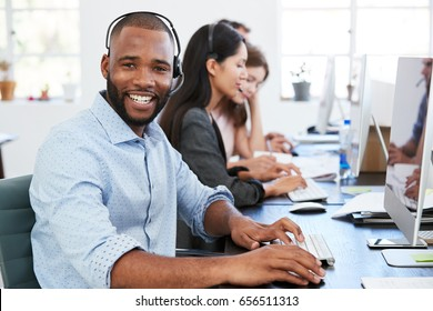 Young black man with headset on smiling to camera in office