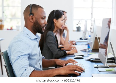 Young black man with headset working at computer in office