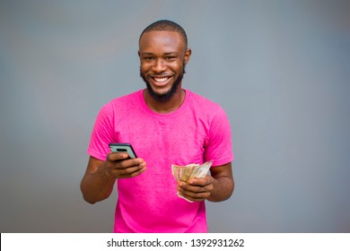 young black man holding some money and a phone with a happy face