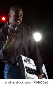 Young black man with a keyboard and headphones over black background.