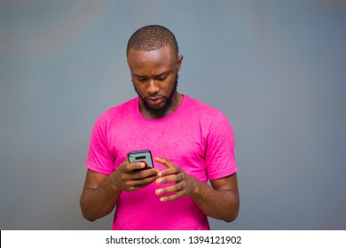 young black man looking unhappy and pressing his phone