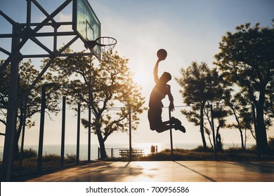 young black man on basketball court, playing with ball