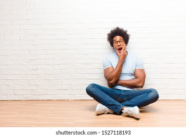 young black man open-mouthed in shock and disbelief, with hand on cheek and arm crossed, feeling stupefied and amazed sitting on the floor at home