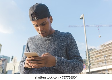 Young black man outdoor using smart phone - technology, social network, communication concept