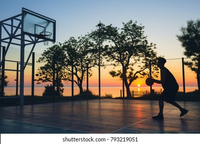 young black man playing basketball on court, morning exercises, active lifestyle, doing sports on sunrise, silhouette
