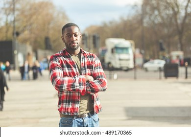 Young black man portrait in London. He is standing with crossed arms and looking at camera, wearing a checked shirt and blue jeans.