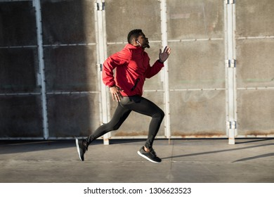 Young black man running fast in the city.