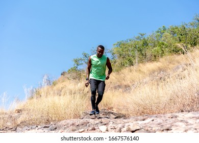 Young Black Man Running at Forest Trail. Sportive man Training Outdoors.American man Running Outside in Forest