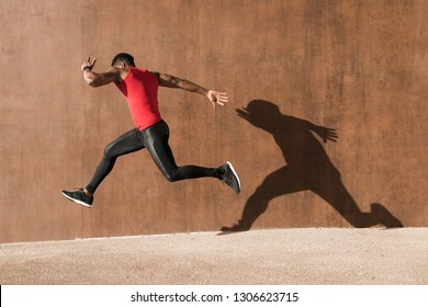 Young black man running and jumping casting shadow on a wall.