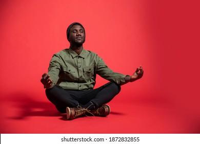 Young black man sitting crosslegged meditating on isolated studio background. Full length.