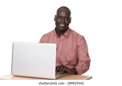 young black man sitting at a laptop looking into the camera on a white background in studio