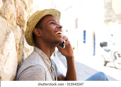 Young black man smiling and talking on mobile phone outside