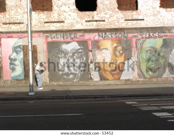 young black man standing on street in front of large mural