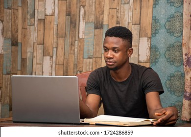 young black man studying at home using his laptop, receiving lectures online
