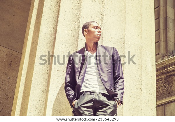 Young black man thinking outside. Wearing a white under wear, fashionable jacket, two hands in pockets, a young black college student is standing under strong sun light, looking forward, thinking.