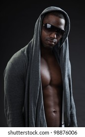 Young black man urban style wearing dark sunglasses looking tough isolated on dark background. Studio portrait.
