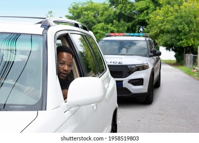 Young black man with a very worried look on his face is looking at the police car that has pulled him over in his rearview mirror reflecting the problems between citizens and some police departments. - Shutterstock ID 1958519803