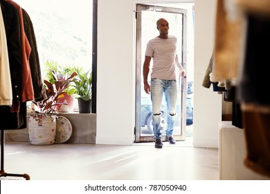 Young black man walking into a clothes shop and closing door