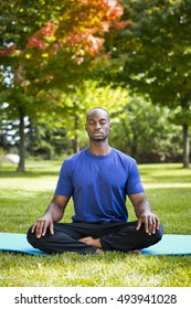 young black man wearing athletic wear sitting in the park exercising yoga