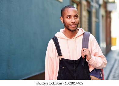 Young black man wearing casual clothes walking smiling down the street. Millennial african guy with bib pants outdoors