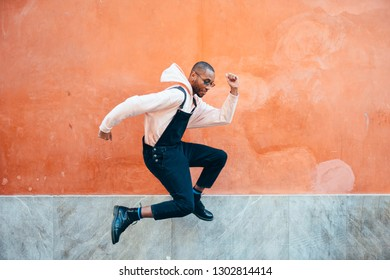 Young black man wearing casual clothes jumping in urban background. Lifestyle concept. Millennial african guy with bib pants outdoors