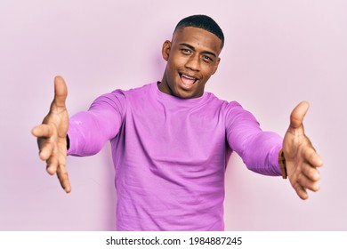 Young black man wearing casual pink sweater looking at the camera smiling with open arms for hug. cheerful expression embracing happiness.