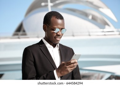 Young black man wearing black elegant suit and fashionable round sunglasses standing against cityscape holding cell phone in hands reading attentively messages having engaging smile.Technology concept