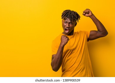 Young black man wearing rastas over yellow background raising fist after a victory, winner concept.