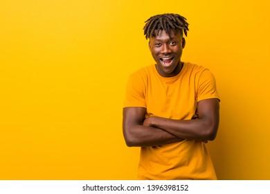 Young black man wearing rastas over yellow background laughing and having fun.