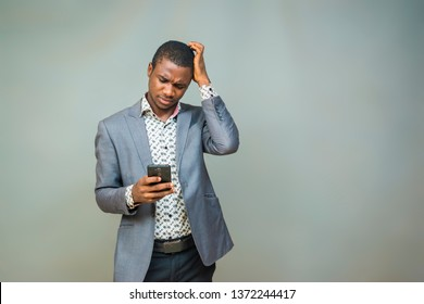 young black man wearing a suit holding his phone and scratching his head worried and confused about something