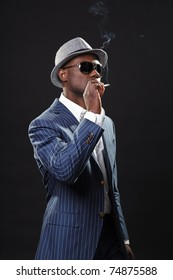 Young black man wearing suit and hat and sunglasses. Smoking a cigarette.