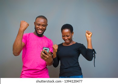 young black man and woman jubilating over something on their phone