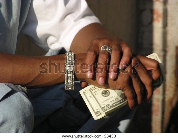 young black man's hands with jewelry and plenty of money