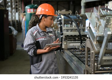 A young black manufacturing worker controls an assembly line in a factory, making notes on a tablet. Young woman in hard hat watches the work process