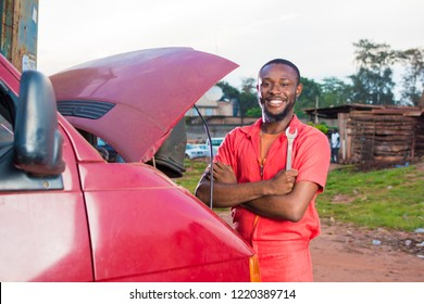young black mechanic man smiling and holding a spanner in front of a van with the engine hood opened in a mechanic site workshop