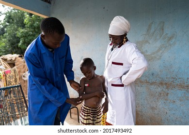 Young black medical assistenst is taking the temperature of a small toddler during a home visit, under the close supervision of a female pediatrician during health screening of children in a village
