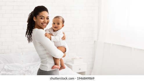 Young Black Mom Holding Baby Toddler, Hugging Carrying Adorable Little Son Posing Standing Indoors. Child Care, Motherhood And Maternity Leave Concept. Panorama, Empty Space For Text