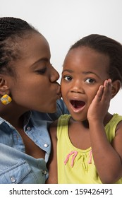 Young Black Mom kissing her daughter