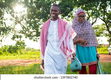 young black muslim man and woman smiling while walking in a park carrying mat and a kettle for prayers